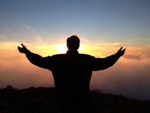 A silhouette of a person, arms upraised, against a sunset.