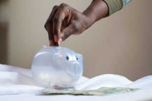 A hand putting a coin into a translucent piggy bank.