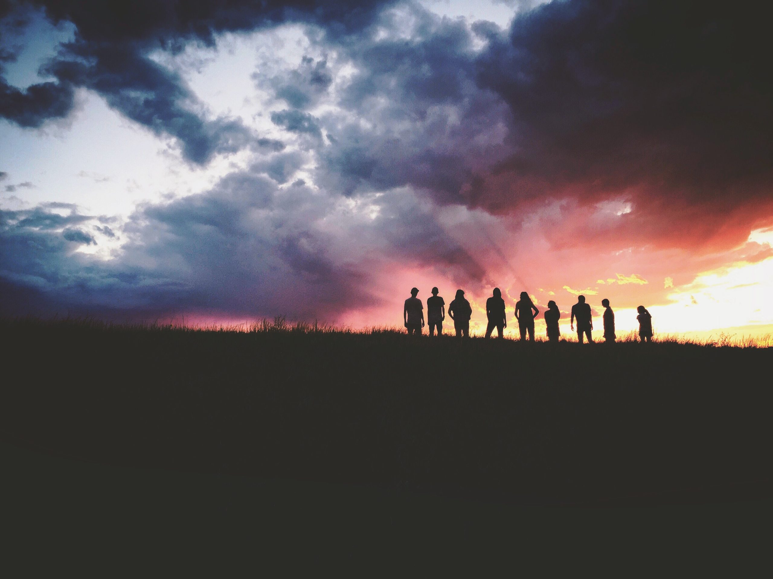 A line of people silhouetted against a lovely sunset.