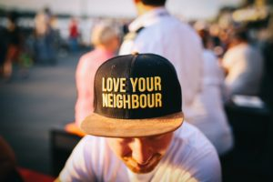 "A person wearing a ball cap with the words ""Love your neighbour"""