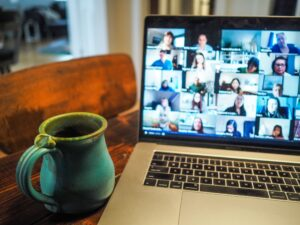 A laptop with faces in squares on the screen. A blue pottery mug sits by the keyboard.