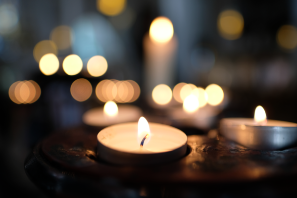 A lit tealight candle with other points of light in the background.